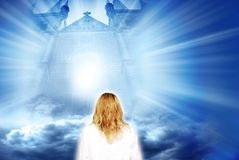 Mystical gate. Woman in white near gate with clouds and divine light Stock Images