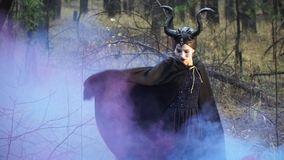 Mystical girl in the image Maleficent dancing among the colored smoke