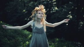Mystical girl in the woods hold a ritual. She dressed in long dresses with wreath on the head. Witches, esoteric