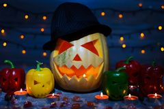 Mystical holiday. Trick or treat. Halloween pumpkin in a hat. Ca. Ndles, flame, candies, sweets, bokeh effect, curved faces royalty free stock photo