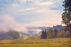 Mystical landscape with sunrise and morning fog in the mountains Royalty Free Stock Images