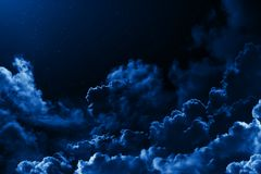 Mystical midnight sky with stars surrounded by dramatic clouds. Dark natural background night starry cloudy sky. Moonlit clouds