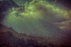 Mystical mountain's village landscape with fog. Royalty Free Stock Image