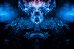 The mystical and mysterious pattern of evaporating blue smoke on a black background is similar in design to an alien head and eyes. Rising to the top in pink royalty free stock image