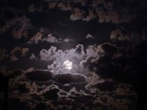 Mystical night sky landscape with white full moon inside of clouds stock photo