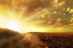 The mystical path toward the hill. A country road leads the eye over the fiery hill from a sunrise and a spectacular sky stock image