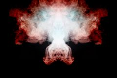 A mystical pattern of colored smoke of red and white in the shape of a ghost`s face with fangs creating a feeling of fear on a. Black isolated background from a royalty free stock image