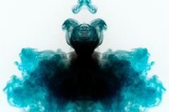 Mystical pattern of multi-colored smoke in black and blue in the form of a ghost with a black body creating a feeling of fear on a. White background from a royalty free stock photos