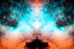 Mystical pattern of orange and blue colored smoke in the shape of a ghost`s face with big eyes and an open mouth creating a. Feeling of fear on a black isolated stock images