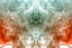 Mystical pattern of orange and blue colored smoke in the shape of a ghost`s face with big eyes and an open mouth creating a. Feeling of fear on a white isolated stock images