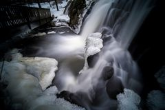 Mystical picture of small waterfall with ice on it. Shot with a fast wide angle lens and long exposure in Helsinki, Finland royalty free stock photos