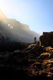 Mystical raylights. Fisherman on the lower right side being bathed with morning ray lights through the mystical fog over the rocky shore Stock Photo