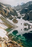 Mystical reflection of snow and mountains in water of Czarny Staw Black Pond, Tatra Mountains, Poland royalty free stock photos