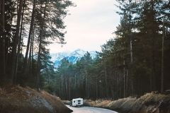 Mystical road in the forest with camper car riding. On it. Mountains on background. Innsbruck, Austria royalty free stock photo