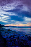 Mystical Seaside Evening. Blue, cloudy and calm evening in a mystical seaside environment of the Marmara region of Turkey. Skyline of a small town on the horizon Stock Images