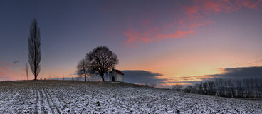 Mystical sunset. Sunset on frozen field with a chapel stock images