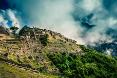 Mystical view on the Machu Picchu city ruins covered with dramatic clouds. Sacred city of Inca during the sunset stock image