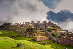 Mystical view on the Machu Picchu city ruins covered with fog. With sun rays passing trough the clouds. Sacred city of Inca during the sunrise royalty free stock photography