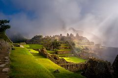 Mystical view on the Machu Picchu city ruins covered with fog. With sun rays passing trough the clouds. Sacred city of Inca during the sunrise royalty free stock images