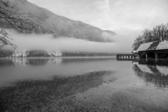 Mystical winter nature. With wooden pier on beautiful lake Bohinj, mountains in background and white mist above the water royalty free stock images