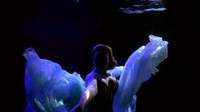 Mystical woman is diving in dark deepness of ocean, fantasy subaquatic shot