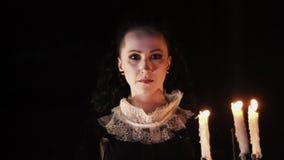 Mystical woman in victorian dress looking in dark room with candelabrum. Mystical caucasian woman in victorian style dress looking in dark room with candelabrum stock video