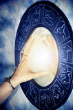 Mystical zodiac. Beautiful female hand touching magic mirror with zodiac symbols and light royalty free stock photography