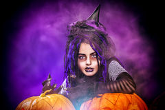 Mysticism girl. Little girl in a costume of witch posing with pumpkins over dark background Royalty Free Stock Photos