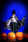 Mysticism. Little boy in halloween costume posing with pumpkins. Over dark background Royalty Free Stock Photos