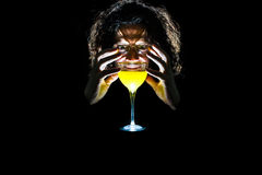 Mysticism and a man with a glass of yellow. Man looks at a glass on a black background Stock Photos