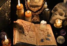 Mysticusachtergrond met zwarte kunstboek, brandende kaarsen en mirrow Stock Fotografie