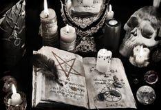 Mysticusachtergrond met zwarte kunstboek, brandende kaarsen en mirrow Royalty-vrije Stock Foto