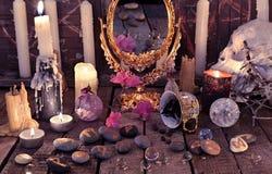 Mysticusstilleven met koffiekop, schedel, brandende kaarsen en steenrunen Royalty-vrije Stock Foto's