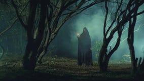 Mystiek meisje in een donker bos met een kaars
