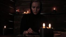 Mystieke mooie non in een zwarte kleding, waarzegging op kaarten met zwart kaarslicht stock footage