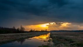 Mystieke zonsondergang zonneschijnlicht de aarde wegens donkere wolken Stock Afbeeldingen