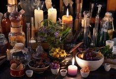 Mystikerstilleben med örter, flaskor, stearinljus och flaskor Royaltyfri Bild