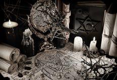 Mystikerstilleben med demonmanuskriptet och magiska böcker i grunge utformar Arkivbild