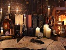 Mystikerstilleben med magi anmärker, bokar och stearinljus Arkivfoto