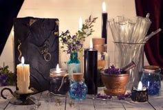 Mystische Gegenstände, schwarze Kerzen, magische Buch- und Glasflaschen auf Planken Lizenzfreie Stockfotografie