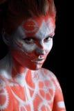 Mystische junge Frau mit gemaltem Gesicht Lizenzfreies Stockfoto