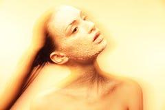 Mystische junge Frau mit kreativem goldenem Make-up Stockfoto