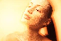 Mystische junge Frau mit kreativem goldenem Make-up Stockbild