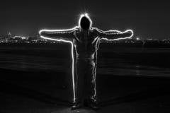 Mystischer schwarzer mit Kapuze Mann, der in der Dunkelheit steht stockbilder