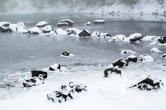 Mystischer Wintersteingarten auf dem kleinen gefrorenen See Stockfotografie