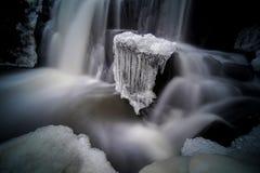 Mystisches Bild des kleinen Wasserfalls mit Eis auf ihm stockfotografie