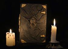 Mystisches Stillleben mit Buch der schwarzen Magie und zwei brennenden Kerzen Stockbild