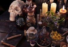Mystisches Stillleben mit dem Schädel, den Kerzen, Flasche und Weinleseflaschen Stockfotos