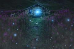 Mystisk bergkabin med magiska ljus arkivfoto