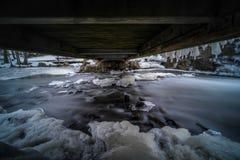 Mystisk bild av vatten som flödar under den lilla bron med is och kallt väder arkivfoton